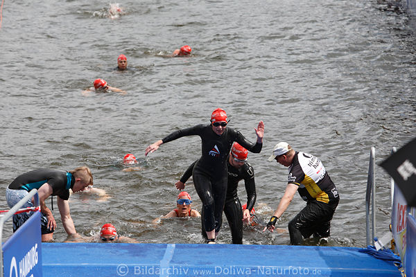 triathlon hamburg foto frau schwimmerin am ziel aus wasser laufen vor anderen schwimmer in bild. Black Bedroom Furniture Sets. Home Design Ideas